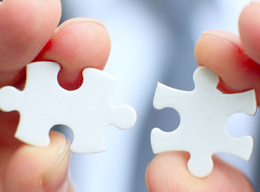 Two jigsaw pieces which fit together.