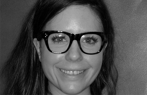 A close-up of a patient with dark hair and glasses smiling to show her teeth before dental treatment with Digital Smile Design.