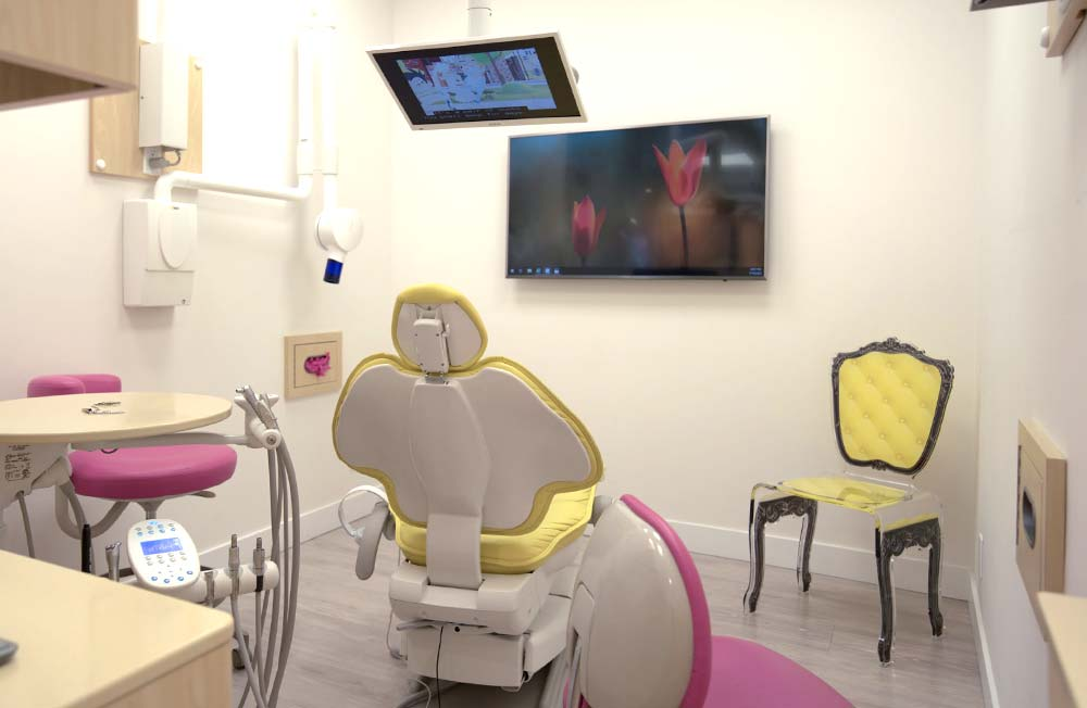 A treatment room at Ironwood Dental Care with a yellow dental chair, pink chairs and an overhead television screen.